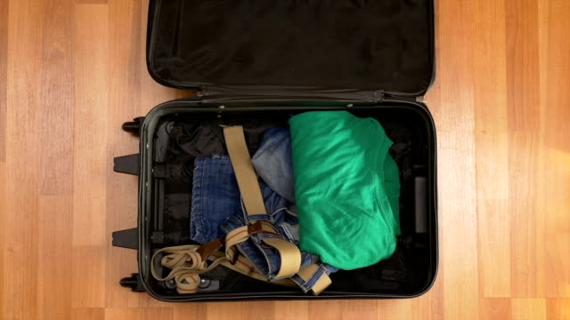 Man hurrying up to pack clothes into travel suitcase