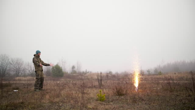 Man ignites hundreds of sparklers on the autumn field, foggy day Man ignites hundreds of sparklers on the autumn field, foggy day. pyrotechnic effects stock videos & royalty-free footage
