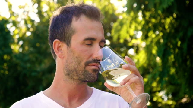 A man immersed in nature at sunset, smells and tastes a glass of white wine and delivers all of his properties.