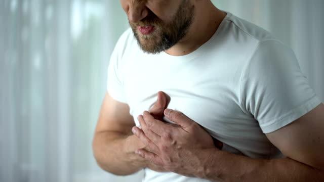 vídeos de stock e filmes b-roll de man in 40s feeling strong chest pain, heart attack caused by stress, cardiology - ataque cardíaco