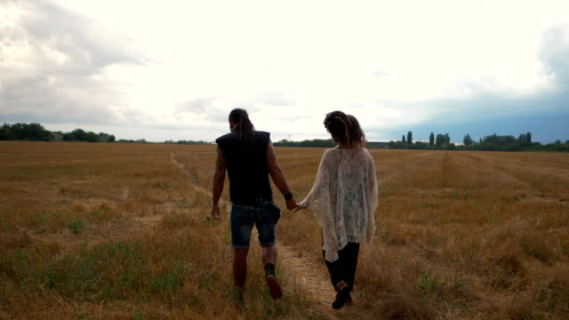 Man in a black cloth and pregnant woman in long dress with dreadlocks walking in wheat field on stormy sky background. Love story. Informal people with tattoo and piercing. Slow motion video