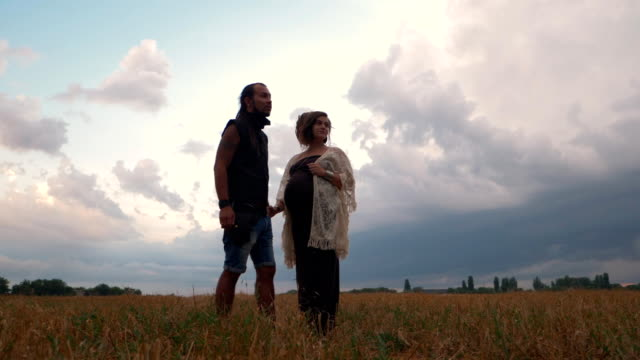 Man in a black cloth and pregnant woman in long dress with dreadlocks walking in wheat field on dramatic sky background. Love story. Informal people with tattoo and piercing. Slow motion video