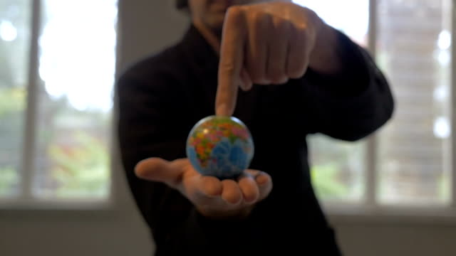 A man in a business sports coat with the world in his hands video