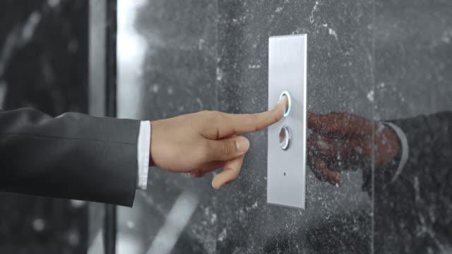 SLO, MO, DS Mann in business-Anzug bügeln Aufzug Knopf – Video