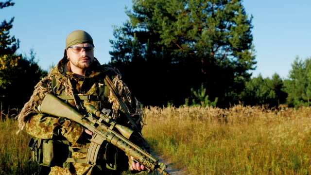 A man in a camouflage bandanna and walking along a country road. In the hands holding weapons video