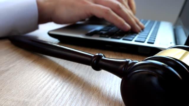vídeos y material grabado en eventos de stock de hombre en un tribunal de escribir en un teclado. martillo y ordenador portátil en un escritorio. - abogado