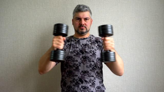 vídeos de stock, filmes e b-roll de um homem de camiseta escura está envolvido em halteres. - comodidades para lazer