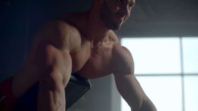 ein mann in einem fitness-club zieht eine langhantel in einer neigung durchführung übungen für die muskeln der wirbelsäule - turngerät mit holm stock-videos und b-roll-filmmaterial