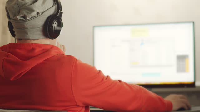 A man in a gray hat and headphones works on a computer, reflection on the wall, remote work