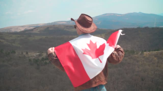 a man in a hat and sunglasses, a leather jacket and jeans threw a canadian flag on his back. - canada day stock videos & royalty-free footage