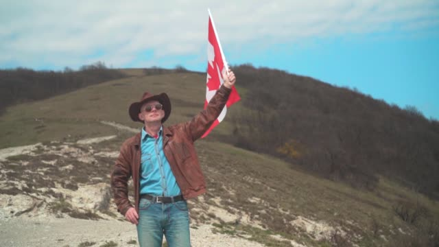 a man in a hat and sunglasses, leather jacket and jeans holding a canadian flag. - canada day stock videos & royalty-free footage