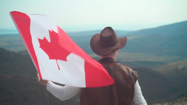 a man in a hat, vest and leather jacket and jeans holds a canadian flag. a man stands with his back in the frame. - canada day stock videos & royalty-free footage
