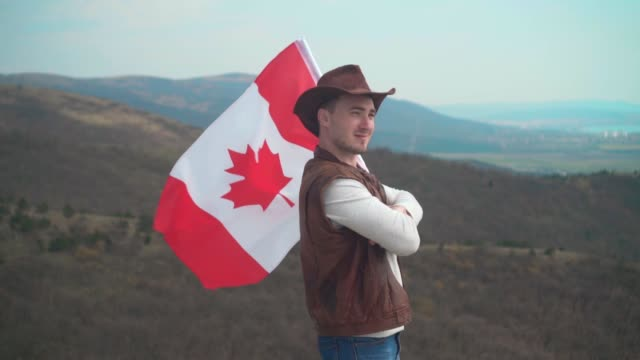 a man in a hat, vest and leather jacket and jeans is holding a canadian flag. flag of canada develops in the wind. - canada day stock videos & royalty-free footage