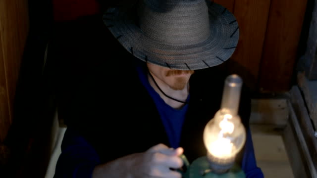 vídeos de stock e filmes b-roll de man in a hat with a kerosene lamp climbs into the attic. he raises his hat and smiles. - inflamável