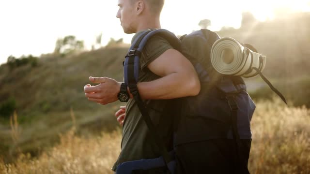 a man in a hike, take off a large backpack from his shoulders and puts it on the ground. having a rest. hiking, active rest concept - viaggiare zaino in spalla video stock e b–roll