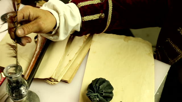 Man in a historical costume writing pen on paper video