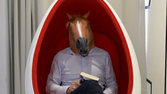 Man in a horse mask showing yes sign in 4k