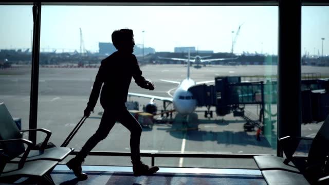 stockvideo's en b-roll-footage met man in een haast reizen met bagage op gang doorvoer - vliegveld vertrekhal