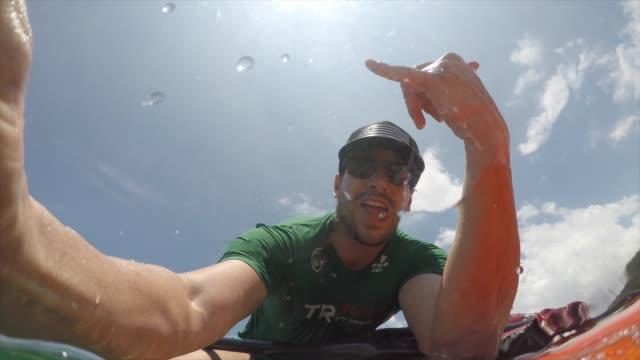 mannen i en kajak på havet tar en selfie - endast en man i 30 årsåldern bildbanksvideor och videomaterial från bakom kulisserna