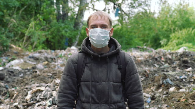 Man in a Mask Standing Near the Garbage Pile