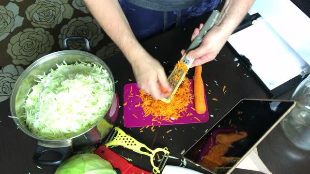 un uomo in una maschera medica trasmette il processo di tagliare le carote tramite collegamento video. crauti a casa durante una pandemia. - braccio umano video stock e b–roll