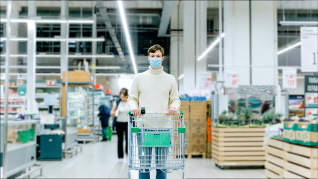 A man in a medical mask stands with a grocery cart in a supermarket, timelapse. Protection from coronavirus, purchase of essential goods - vídeo