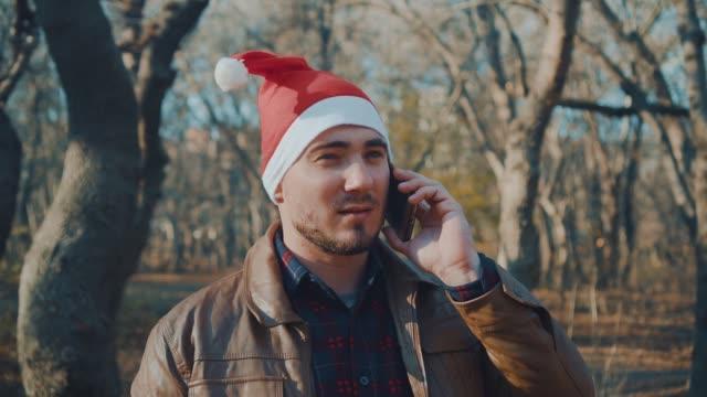 en man i en ny år hatt pratar i telefon. samtal och önskar en god jul. - endast en medelålders man bildbanksvideor och videomaterial från bakom kulisserna