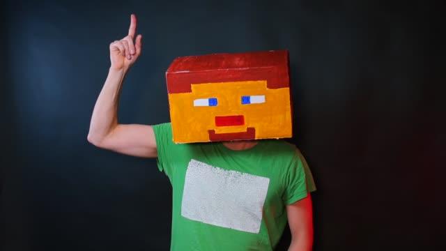 ein mann in einer bemalten maske steve kratzt sich am kopf. zeigt geste gibt es idee - kind isometric stock-videos und b-roll-filmmaterial