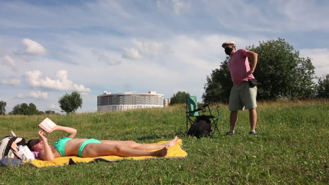 a man in a protective mask and cap sits in a camping chair. a woman is sunbathing on the ground and looking at the phone. outdoor recreation in self-isolation during a pandemic. - grass isolated video stock e b–roll