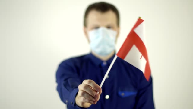 Video A man in a protective mask on his face against the virus waving the flag of the country of Canada. Country Coronavirus Disease Concept, COVID-2019, pandemic