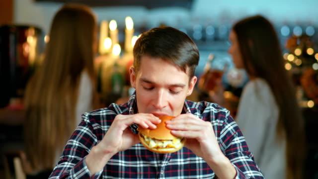 man in a restaurant eating a hamburger and smiling - cheeseburger filmów i materiałów b-roll
