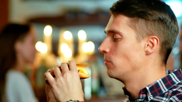 man in a restaurant eating a hamburger - mordere video stock e b–roll