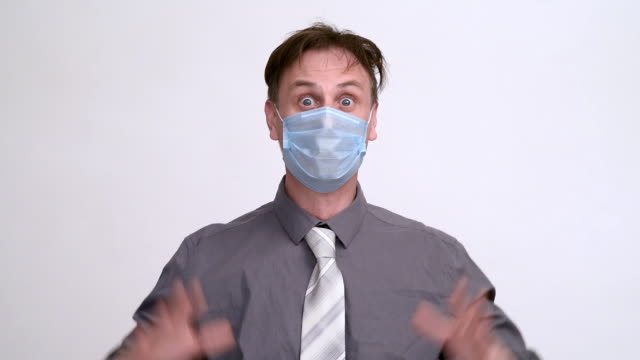 셔츠를 입고 호흡보호구 마스크를 쓴 넥타이를 매고 있는 남자가 밝은 배경에 머리를 쥐고 있다. 코로나 바이러스 글로벌 두려움과 공황. - home 스톡 비디오 및 b-롤 화면