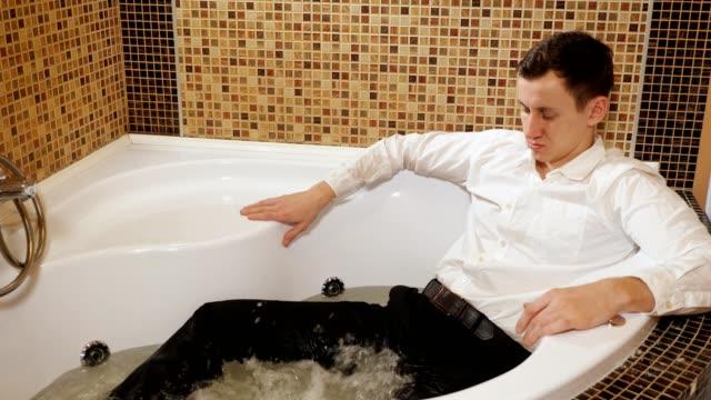 mann in hemd und hose liegt in bad - unterordnung stock-videos und b-roll-filmmaterial