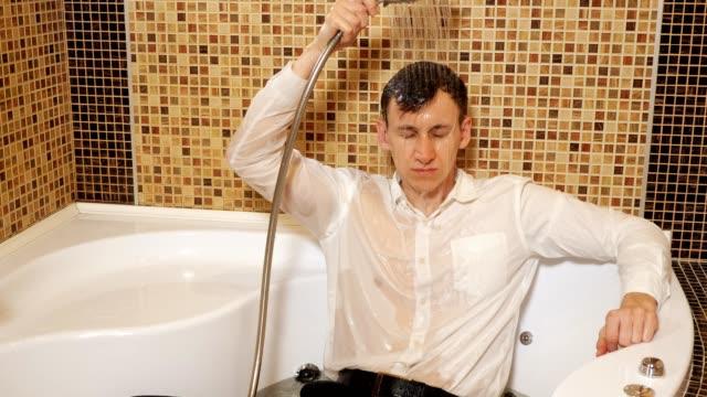 mann in hemd und hose liegt in der badewanne unter der dusche - unterordnung stock-videos und b-roll-filmmaterial