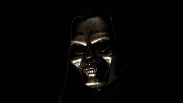 vídeos de stock e filmes b-roll de man in a skeleton mask in the dark - capuz