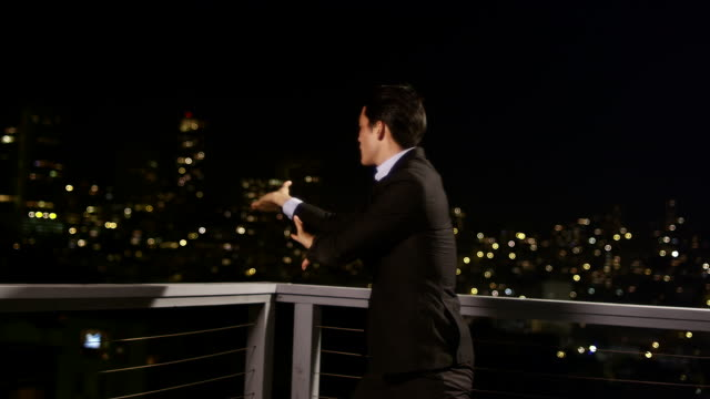 A man in a suit does Tai Chi while standing on a rooftop balcony at night video