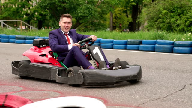 Man in a suit driving Go-Kart car in a playground.