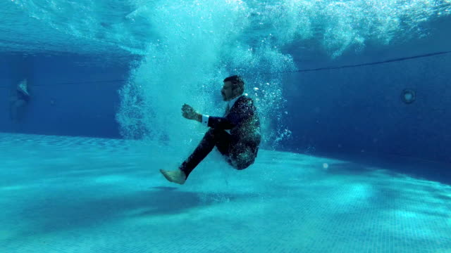 a man in a suit jumps into the pool, tumbles under the water and floats to the surface in a cloud of bubbles. slow motion. underwater photography. 4k. 25 fps. - business suit stock videos & royalty-free footage