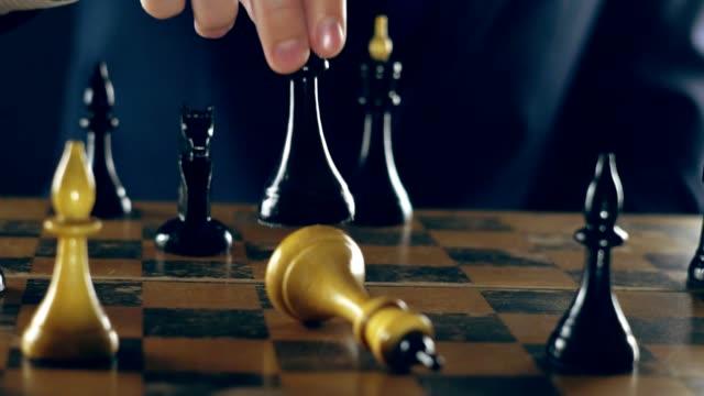 mann in einem anzug spielt schach - könig schachfigur stock-videos und b-roll-filmmaterial