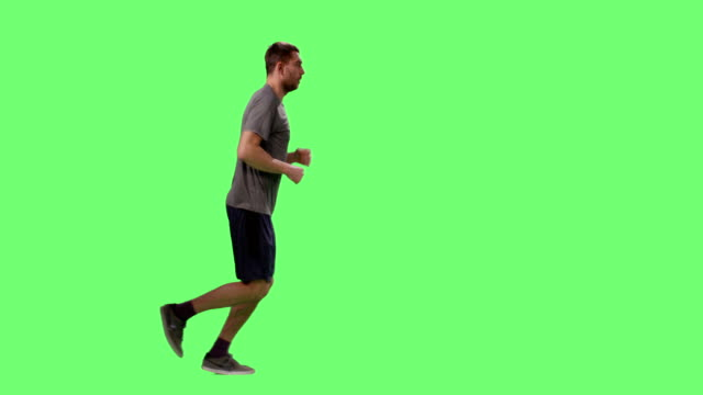 stockvideo's en b-roll-footage met man in een t-shirt is jogging op een mock-up groen scherm op de achtergrond. - green background