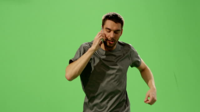 Man in a t-shirt is jogging while speaking on the mobile phone on a mock-up green screen in the background. video