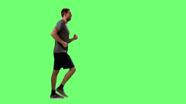 vídeos de stock e filmes b-roll de man in a t-shirt is sport walking on a mock-up green screen in the background. - teeshirt template