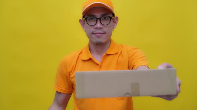 man i en enhetlig hand levererar en paket låda - posttjänsteman bildbanksvideor och videomaterial från bakom kulisserna