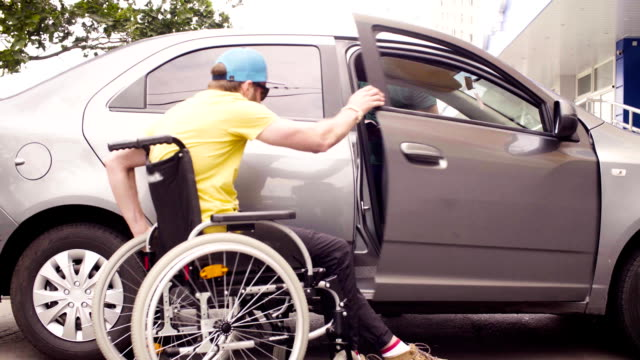 vídeos de stock e filmes b-roll de a man in a wheelchair and a woman near the car - pessoas com deficiência