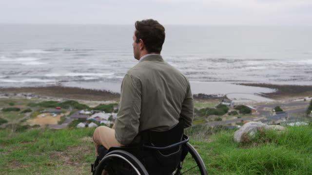 vídeos y material grabado en eventos de stock de hombre en silla de ruedas mirando al mar - deportes en silla de ruedas