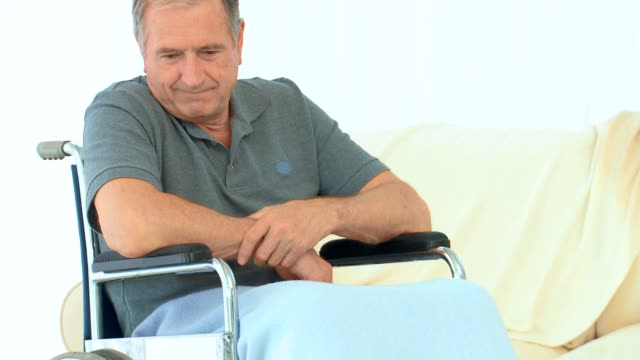 Man in a wheelchair thinking Man in a wheelchair thinking near a sofa amputee stock videos & royalty-free footage