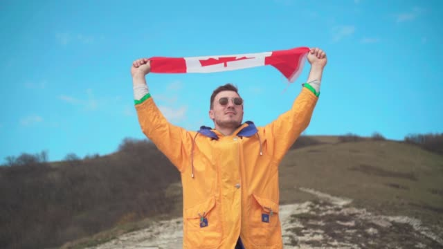 a man in a yellow jacket, blue jeans and glasses stands in the mountains and holds the canadian flag with both hands. - canada day stock videos & royalty-free footage