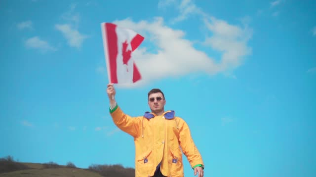 a man in a yellow jacket, blue jeans and glasses stands in the mountains and waves the flag of canada from side to side. - canada day stock videos & royalty-free footage