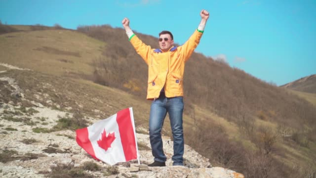 a man in a yellow jacket, blue jeans and glasses stands on a mountain, the flag of canada is set in the ground. - canada day stock videos & royalty-free footage